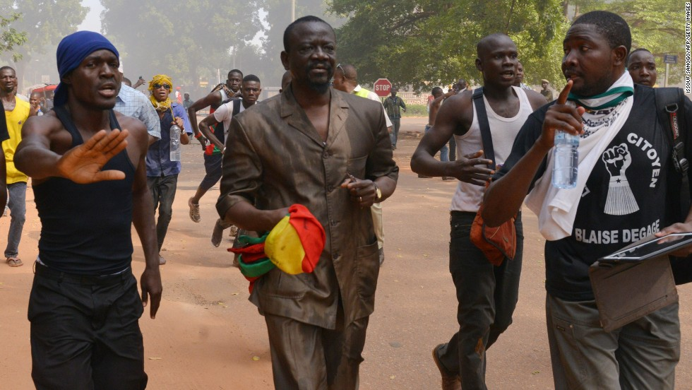 A Burkina Faso deputy clutches a national flag as he flees parliament on October 30.