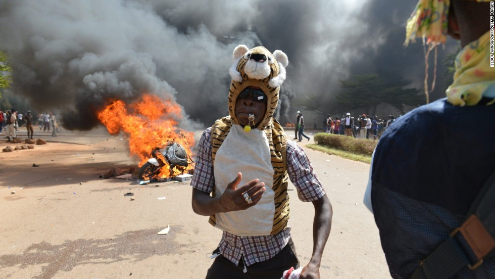 A protester poses in front of a burning car outside of parliament on October 30.