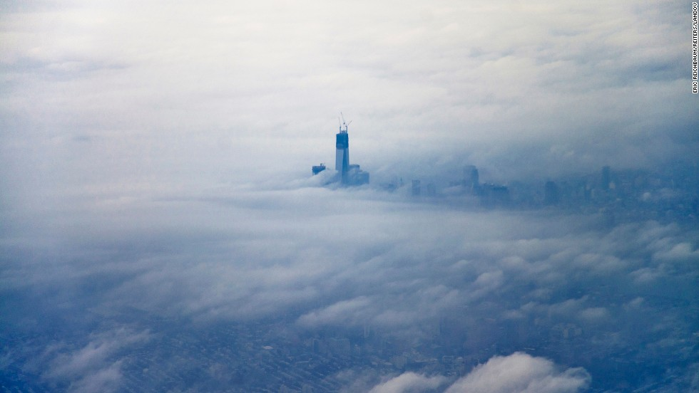 "The newly constructed One World Trade Center building, dubbed ""Freedom Tower,"" rises above the clouds on December 2, 2012, in an aerial photo taken from an airplane leaving New York's LaGuardia Airport."