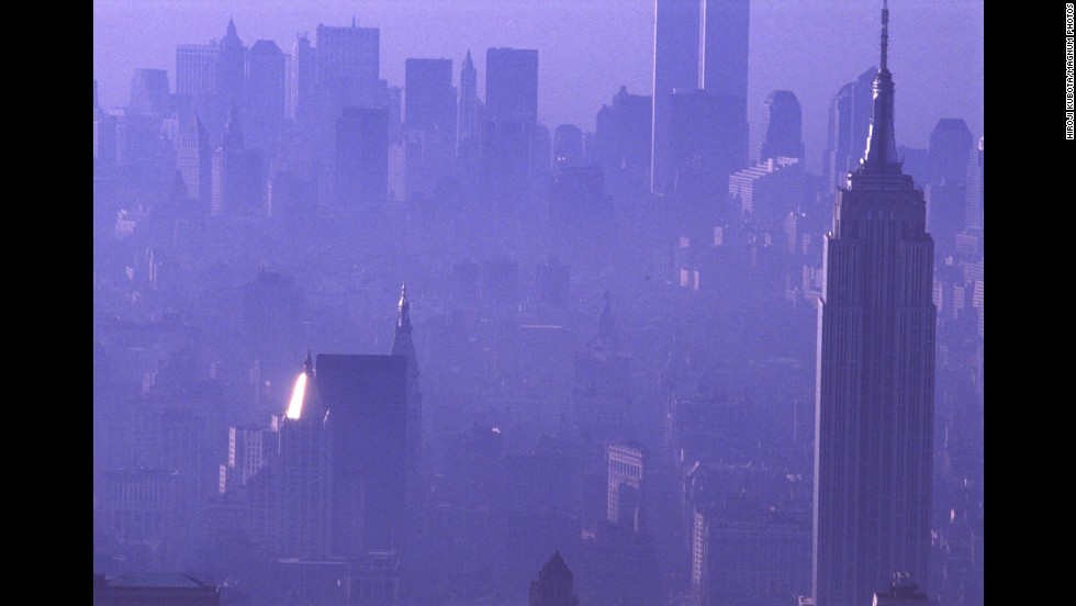 A purple haze enshrouds the city in 1989, with the Empire State Building in the foreground and the Twin Towers in the background.
