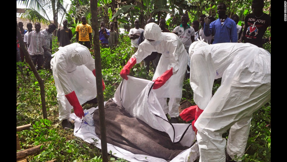 Health workers in Monrovia cover the body of a man suspected of dying from the Ebola virus on October 31, 2014.
