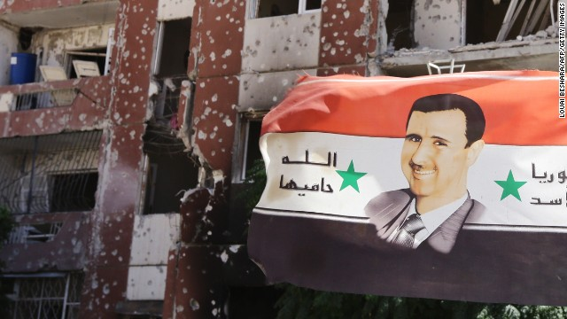Caption:THIS PICTURE WAS TAKEN ON A GOVERNMENT-GUIDED TOUR A flag showing Syrian President Bashar al-Assad flutters near damaged buildings in Adra northeast of the capital Damascus on September 25, 2014. Syrian government troops recaptured an area of the key rebel-held town Adra used to house workers, after securing the highway and the industrial zone, a security source and monitoring group said. AFP PHOTO / LOUAI BESHARA (Photo credit should read LOUAI BESHARA/AFP/Getty Images)