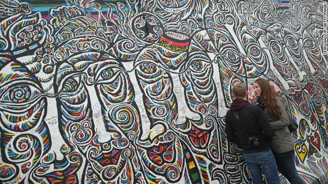 A young couple stand at a still-standing portion of the original Berlin Wall called the East Side Gallery on November 5, 2014 Berlin, Germany.