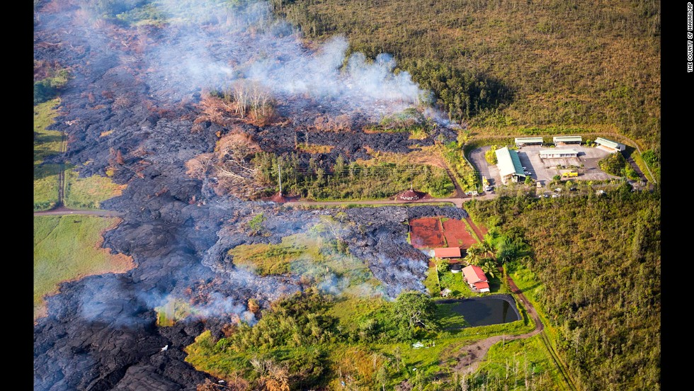 "Lava flows near a residential structure in Pahoa, Hawaii, on Monday, November 10. The lava flow from <a href=""http://www.cnn.com/2014/10/28/us/hawaii-volcano/index.html?hpt=hp_c2"" target=""_blank"">the Kilauea Volcano</a> is advancing on the community of about 950 people on Hawaii's Big Island and claimed its first home in the town, which has been watching the slow-moving flow approach for months."