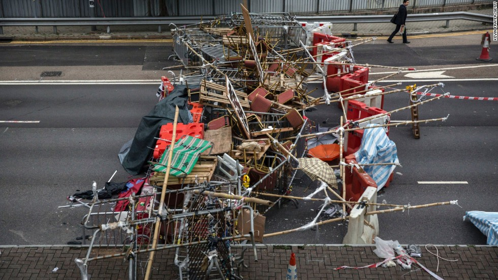 A businessman walks to work past protester-placed barricades that blocked a road at the Admiralty protest site on Thursday, November 13.