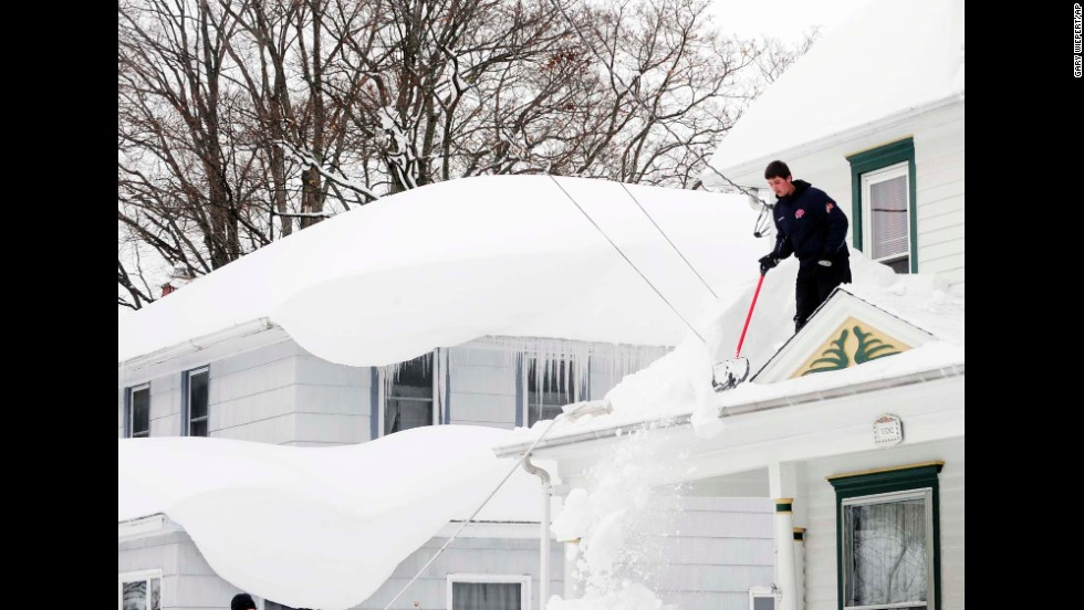 Andrew Zelak cleans snow from his roof in Alden, New York, on November 20.