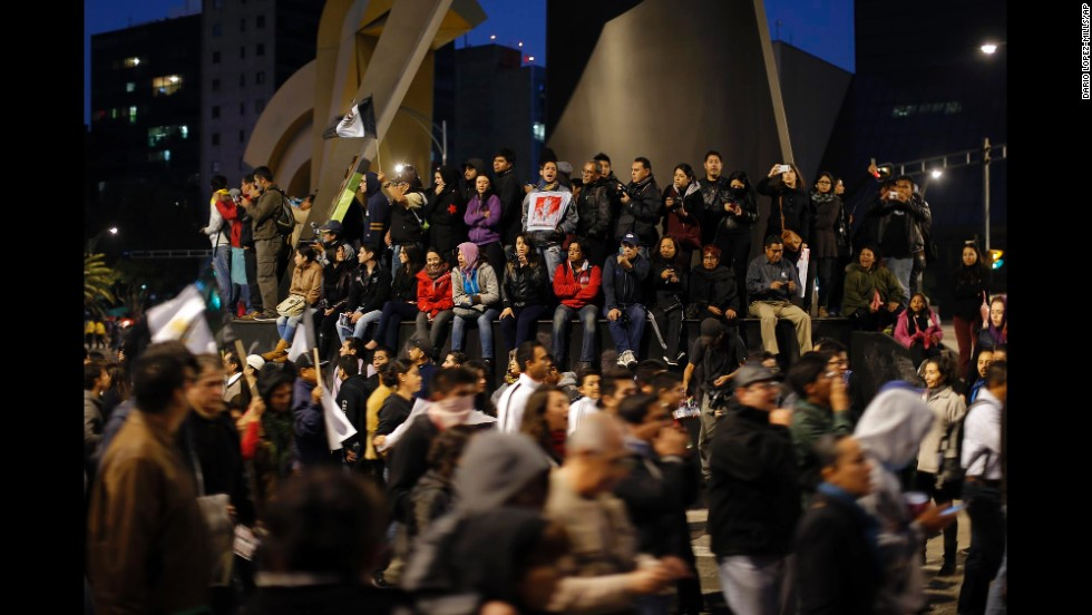 People on the base of a monument watch and cheer on marchers in Mexico City on November 20.