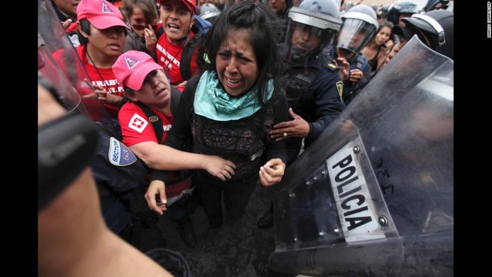A protester cries as police attempt to detain her and human rights observers try to reach her during a march near the Mexico City airport on November 20.