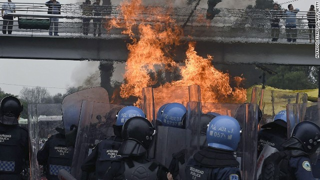 Riot police clash with students furious at the presumed massacre of 43 students, in the surroundings of Mexico City's international airport on November 20.
