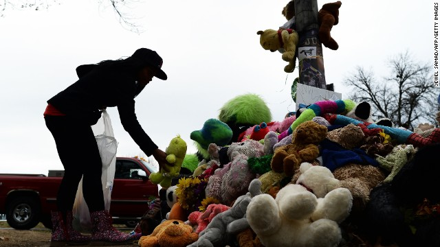In late November, a wellwisher aranges stuffed toys at a makeshift memorial where 18-year-old Michael Brown was shot dead by a Ferguson police office.