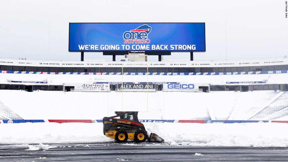 "Workers clear snow from the field at Ralph Wilson Stadium on Sunday, November 23 in Orchard Park, New York. Snowed out at the stadium, the Bills are in Detroit to play their ""home"" NFL football game against the New York Jets on Monday night. Western New York continues to dig out from a lake-effect storm that dumped about a year's worth of snow in three days, trapping residents in their homes and stranding motorists on roadways."