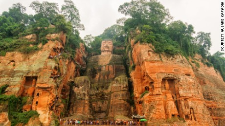 This file photo shows tourists at the feet of the giant Buddha, which is usually untroubled by river water.