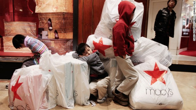 "NEW YORK - NOVEMBER 26:  Children wait with shopping bags inside Macy's department store on ""Black Friday"" shopping day November 26, 2010 in New York City.  Christmas shopping season is officially under way as Thanksgiving ends, and early signs point to a solid turnout for holiday shopping season.  (Photo by Chris Hondros/Getty Images)"