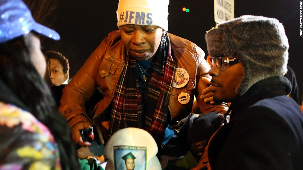 Lesley McSpadden, mother of Michael Brown, is escorted away from the Ferguson Police Department on November 24.
