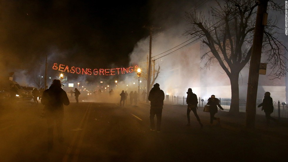 Protesters run away after police deployed tear gas in Ferguson on Monday, November 24.