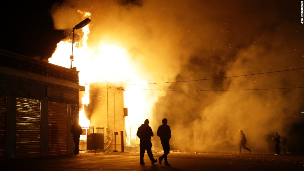 People walk away from a burning storage facility on November 24.
