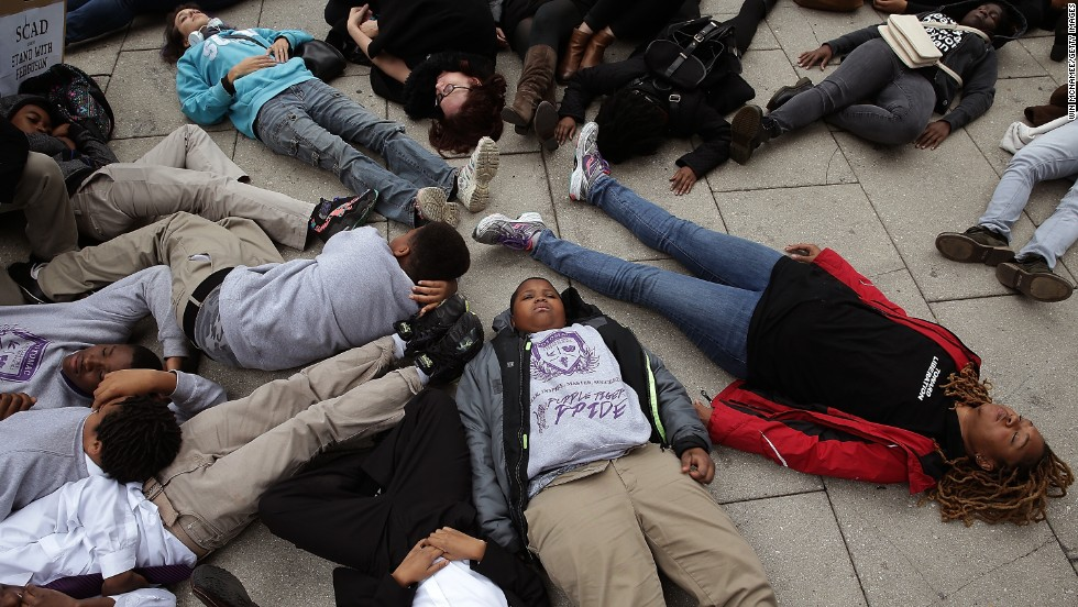 "Schoolchildren from the Potomac Preparatory Charter School take part in a ""die-in"" during a protest outside the Office of Police Complaints as part of a planned ""28 Hours for Mike Brown"" protest November 25 in Washington."