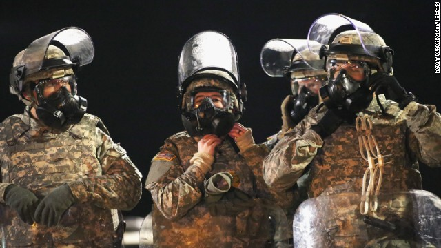 National Guard troops don gas masks while assisting police with controlling demonstrators during a protest in front of the police station on November 25, 2014 in Ferguson, Missouri.