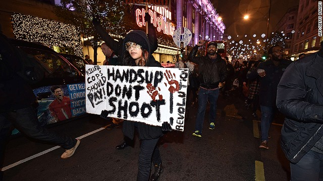 Demonstrators hold up placards and march down Oxford Street in central London on November 26, 2014 during a protest over the US court decision not to charge the policeman who killed unarmed black teenager Michael Brown in the town of Ferguson. The policeman whose killing of unarmed black teenager Michael Brown sparked weeks of riots in the US town of Ferguson will not face charges, the county prosecutor said on November 25, amid mounting anger in the streets. Over a thousand people demonstrated outside the US embassy in London, holding up their hands and waving placards. The demonstration then turned into a march along Oxford Street, one of central London's main retail and shopping streets. AFP PHOTO / LEON NEALLEON NEAL/AFP/Getty Images