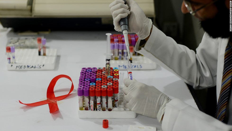 A Pakistani technician takes samples in a laboratory alongside a ribbon promoting World Aids Day in Islamabad on November 30, 2013.