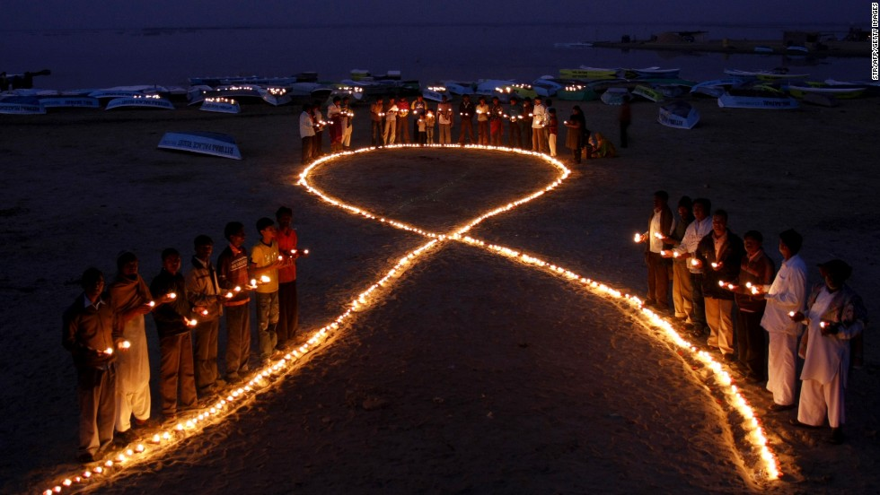 Indian villagers hold oil lamps as they surround a huge AIDS symbol on the beach at Nalsarovar, some 60 km from Ahmedabad, on November 30, 2009 the eve of World Aids Day.