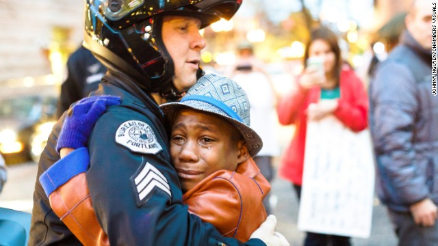 Devonte Hart,12, shares a hug with Sgt. Bret Barnum at Ferguson rally.