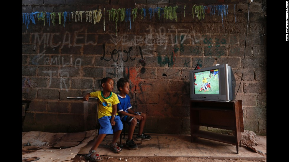 "<strong>June 17:</strong> Boys at a slum on the outskirts of Brasilia, Brazil, watch a World Cup soccer match between Brazil and Mexico. Brazil hosted this year's World Cup, although <a href=""http://www.cnn.com/2014/06/12/world/gallery/world-cup-protests/index.html"">there were protests</a> over whether the money spent on the tournament would have been better used elsewhere."