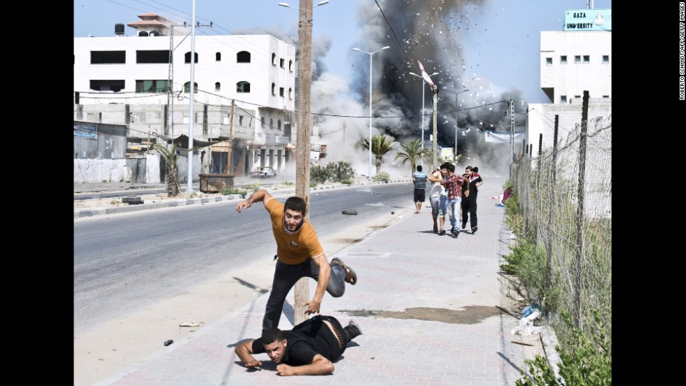 <strong>August 23:</strong> Palestinians run away after a bomb from an Israeli airstrike hit a house in Gaza City.