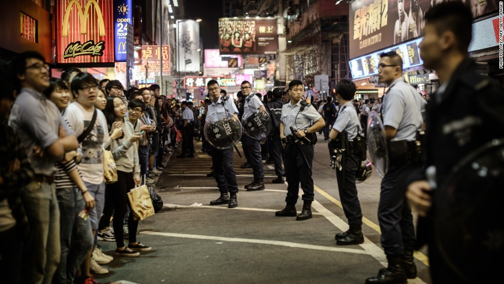 Policemen keep vigil as pro-democracy demonstrators gather on street parallel to where a protest site was cleared in the Mongkok district of Hong Kong on Friday, November 28.