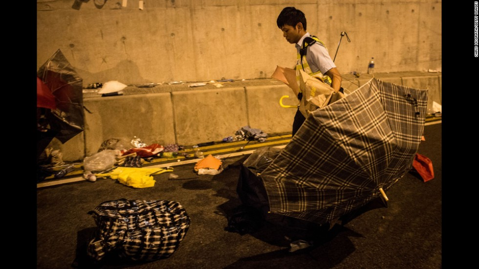 A police officer clears umbrellas from the Lung Wo road tunnel after clashes between protesters and police on December 1.