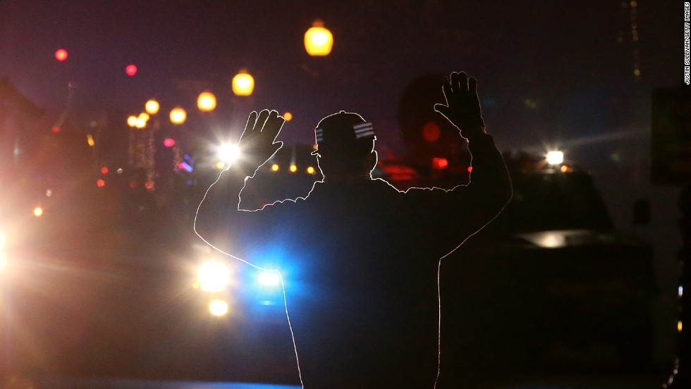 "<strong>November 24:</strong> A protester in Ferguson, Missouri, stands in front of police vehicles with his hands up. A grand jury's decision not to indict police officer Darren Wilson for the killing of Michael Brown prompted <a href=""http://www.cnn.com/2014/11/24/justice/gallery/ferguson-reaction/index.html"">new waves of protests in Ferguson</a> and across the country."