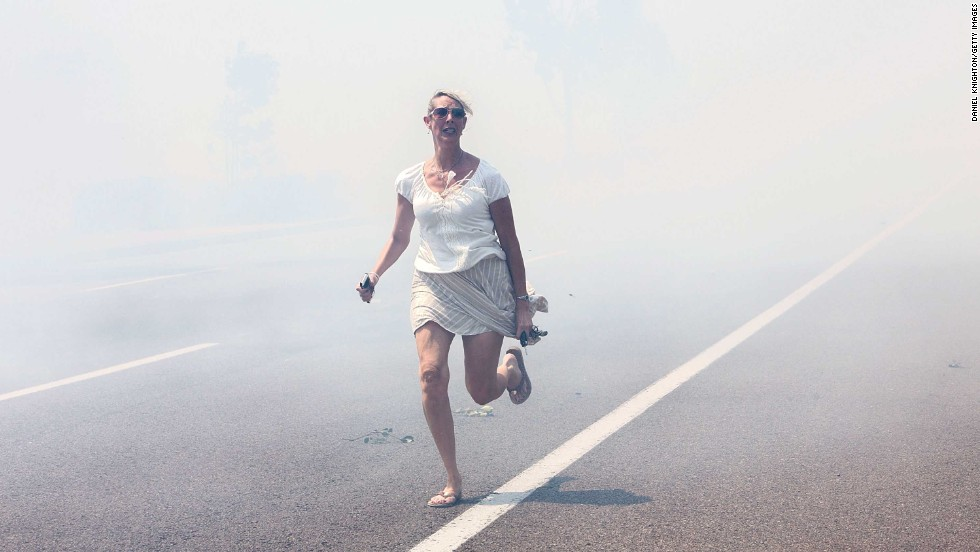 "<strong>May 14:</strong> A woman flees a wildfire as it crosses a highway in Carlsbad, California. <a href=""http://www.cnn.com/2014/05/13/us/gallery/california-wildfire/index.html"">Wildfires forced evacuations in San Diego County</a> after a high-pressure system brought unseasonable heat and gusty winds to the parched state."