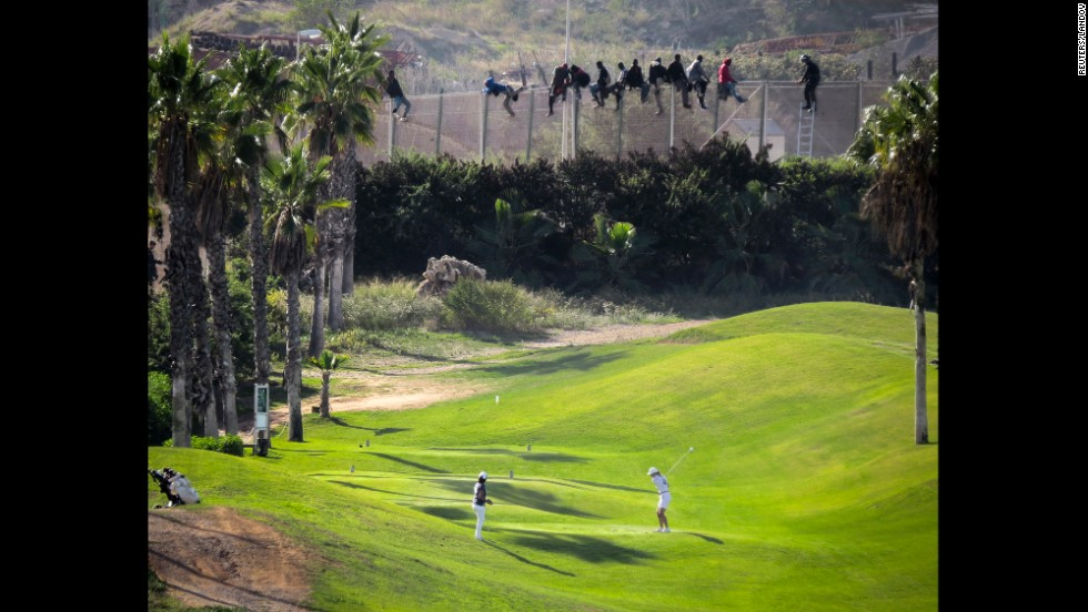 <strong>October 22:</strong> A golfer hits a tee shot as African migrants sit atop a border fence dividing Morocco and the Spanish enclave of Melilla.