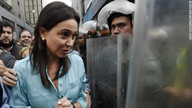Venezuelan opposition leader Maria Corina Machado walks along members of the National Guard in riot gear upon arriving at the prosecutor's office in Caracas on December 3, 2014. Machado, dismissed in March from her deputy seat, must testify about her supposed involvement in an alleged plot to assassinate Venezuelan President Nicolas Maduro. AFP PHOTO/JUAN BARRETO (Photo credit should read JUAN BARRETO/AFP/Getty Images)