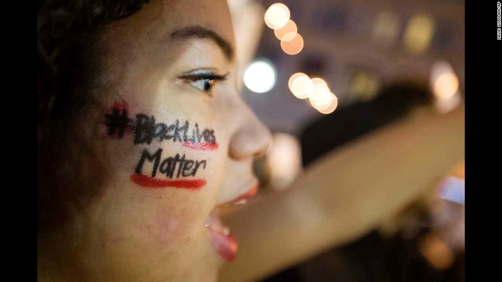 """Black Lives Matter"" is written across the cheek of Samaria Muhammad as she chants with fellow protesters in Atlanta on December 4."