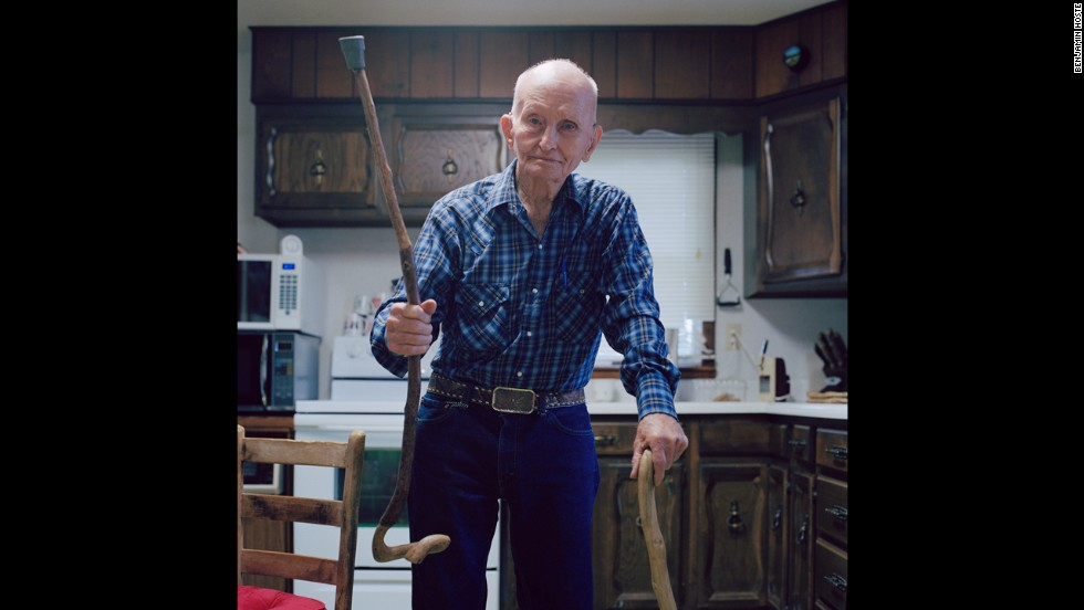 Local resident Bob Morgan holds up one of the many walking sticks he carved himself. Morgan, a World War II veteran and cowboy, was building barns and bending metal into his 80s, Hoste said. He passed away in August at the age of 89.