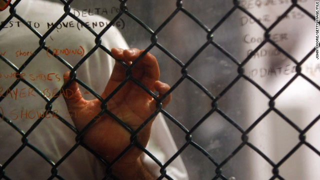 GUANTANAMO BAY, CUBA - OCTOBER 28: (EDITORS NOTE: Image has been reviewed by U.S. Military prior to transmission) A detainee stands at an interior fence at the U.S. military prison for 'enemy combatants' on October 28, 2009 in Guantanamo Bay, Cuba. Although U.S. President Barack Obama pledged in his first executive order last January to close the infamous prison within a year's time, the government has been struggling to try the accused terrorists and to transfer them out ahead of the deadline. Military officials at the prison point to improved living standards and state of the art medical treatment available to detainees, but the facility's international reputation remains tied to the 'enhanced interrogation techniques' such as waterboarding employed under the Bush administration. (Photo by John Moore/Getty Images)