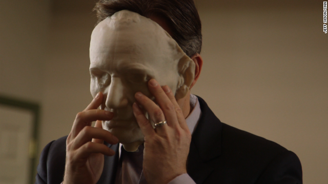 Jake Tapper brings a 3D mask of Abraham Lincoln up to his face.