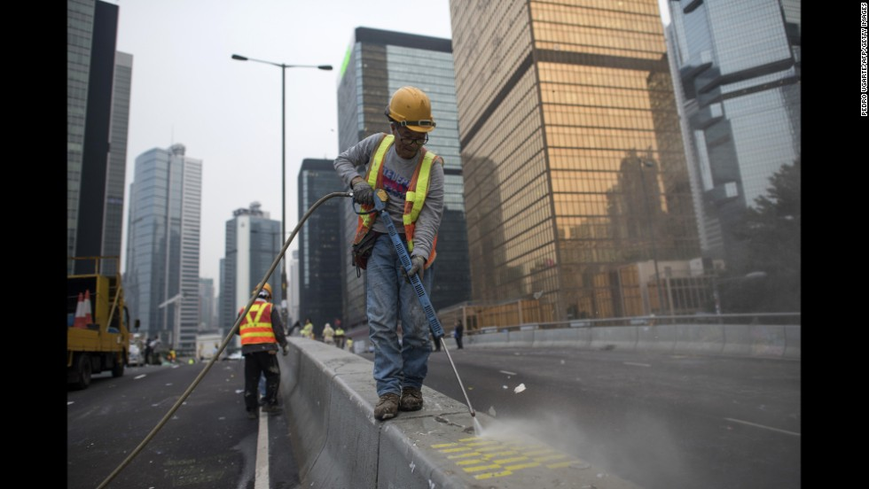 A worker cleans the street after Hong Kong police dismantled the main protest camp December 11.