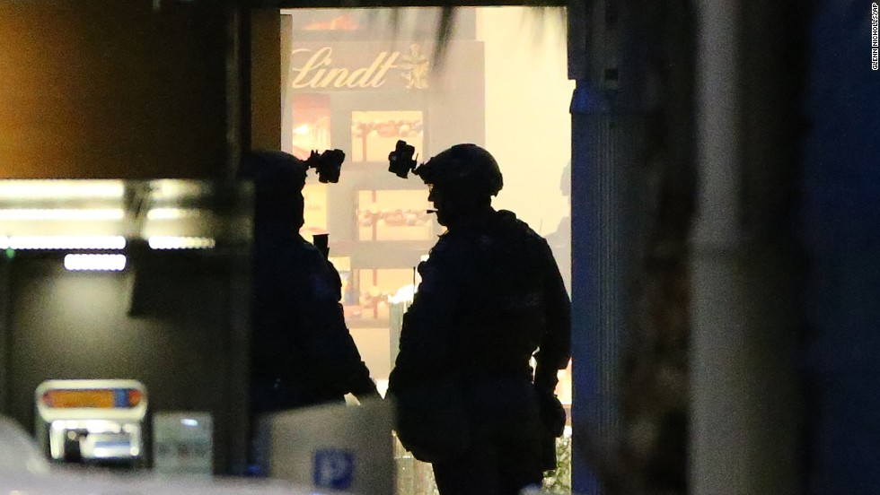 Two armed police officers stand ready to enter the cafe on December 16.