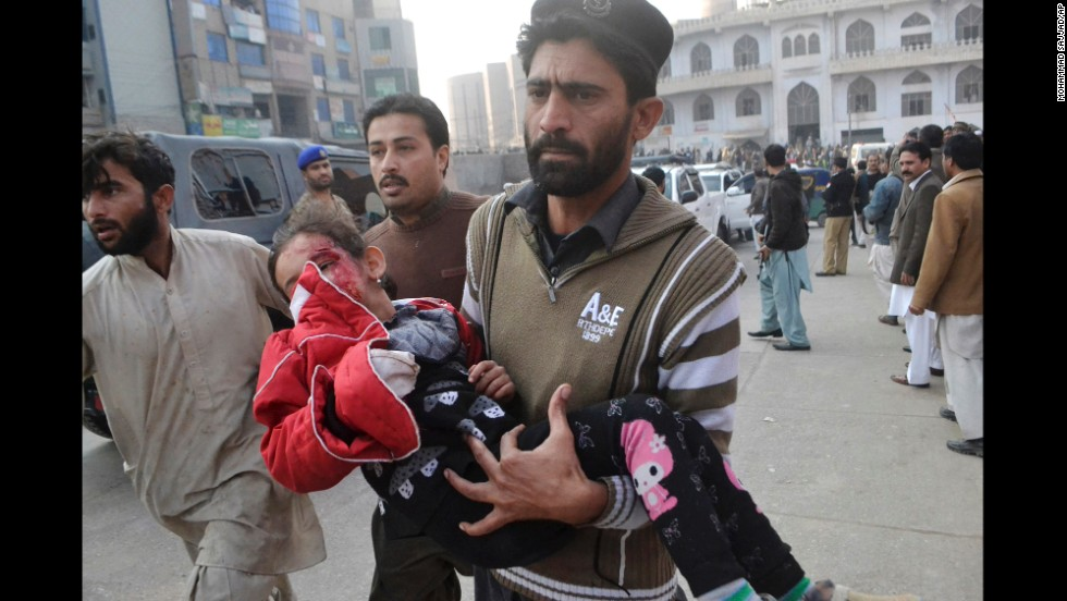 An injured girl gets rushed to a hospital in Peshawar.