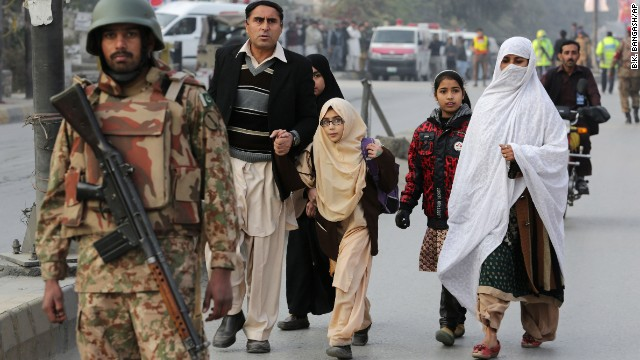 Parents escort their children away from a school in Peshawar, Pakistan, on Tuesday, December 16.
