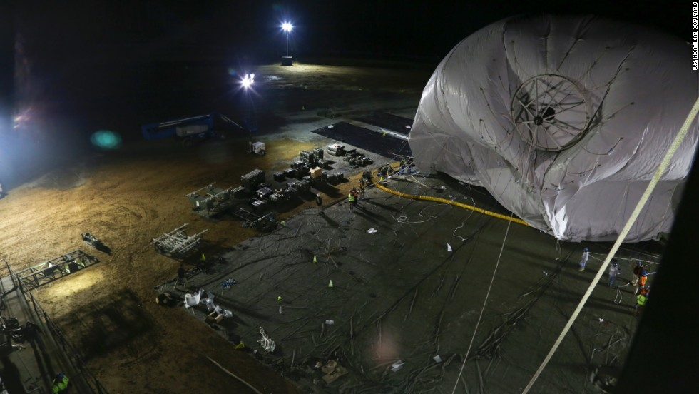 "The U.S. Army is launching two stationary ""blimps"" at 10,000-feet over Maryland to better protect the Washington, D.C., area from cruise missiles and other possible air attacks. On December 14, personnel from the Joint Land Attack Cruise Missile Defense Elevated Netted Sensor System (JLENS) oversee the inflation of an aerostat, or stationary blimp, at Aberdeen Proving Ground, Maryland."