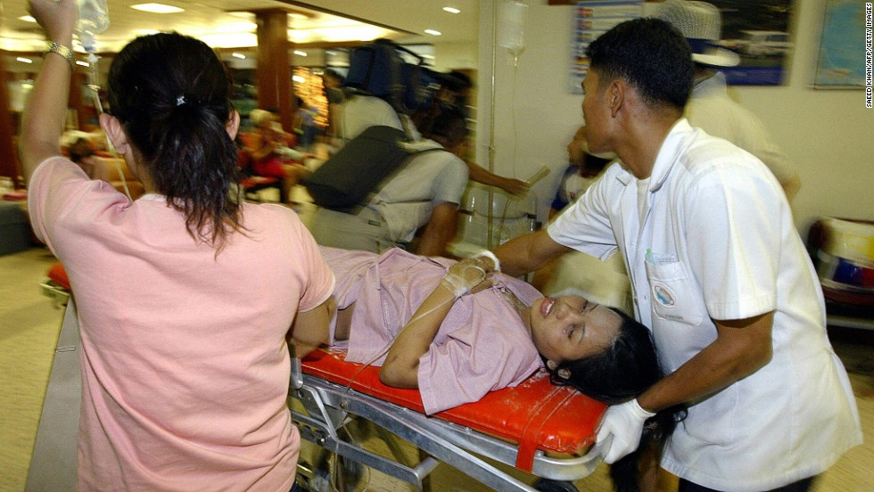 Thai medical staff rush a victim of tidal waves to the operating theater at Phuket International Hospital on December 26, 2004. At least 310 people were killed and more than 5,000 injured in southern Thailand.