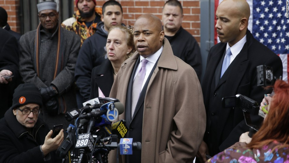 Brooklyn Borough President Eric Adams, third from right, speaks on December 21 while Manhattan Borough President Gale Brewer, fourth from right, and Bronx Borough President Ruben Diaz, right, listen during a news conference at an impromptu memorial near the site where the officers were shot.
