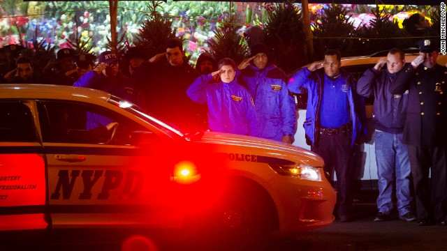 Mourners stand at attention as the bodies of two fallen NYPD police officers are transported from Woodhull Medical Center on Saturday, December 20.