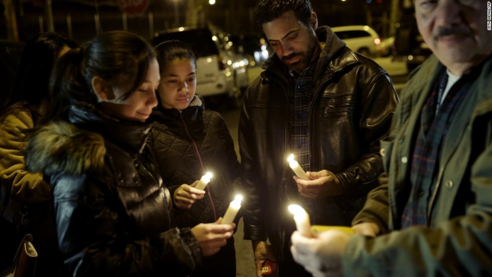 People light candles during a vigil on Sunday, December 21, for two NYPD officers who were ambushed and killed on Saturday. The two NYPD officers, Wenjian Liu and Rafael Ramos, were shot while sitting in their police car. Police have named Ismaaiyl Brinsley as the shooter.