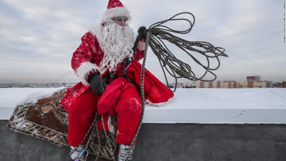 A performer dressed as Father Frost, the Russian equivalent of Santa, rests on a high-rise building Monday, December 22, in Kemerovo, Russia.