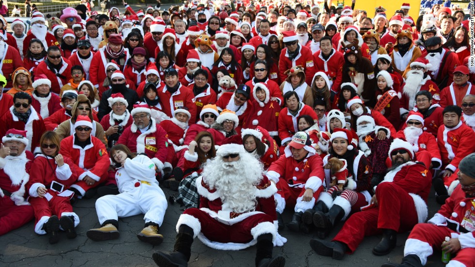 "Motorcyclists in Santa outfits take a group photo before embarking on a Christmas ""toy run"" on their bikes on December 23 in Tokyo."