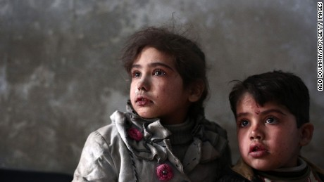 Syrian children look on as they wait for treatment at a makeshift clinic in the besieged rebel town of Douma, on December 21, near Damascus.